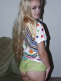 Green panties blonde with perky tits posing in a dimly-lit room