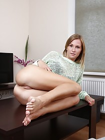 Short-haired blonde with long legs masturbating on top of a table