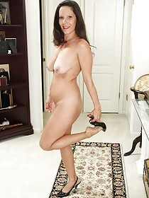 Dark-haired MILF with natural breasts and a black dress shows her body